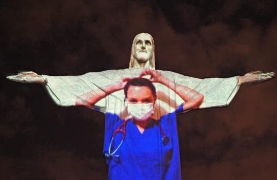 キリスト像に映し出されたコロナウィルス感染拡大と闘う医療従事者の映像