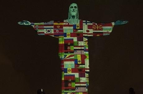 キリスト像に映し出されたコロナウィルス感染拡大と闘う国々の国旗の映像