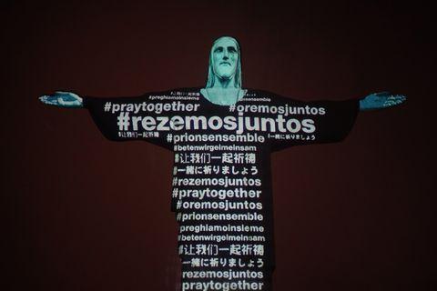 キリスト像に映し出されたコロナウィルス感染拡大と戦う世界中の人々への様々な言語のメッセージ